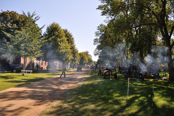 Looking down the road in the park with a lot of steam engine exhaust